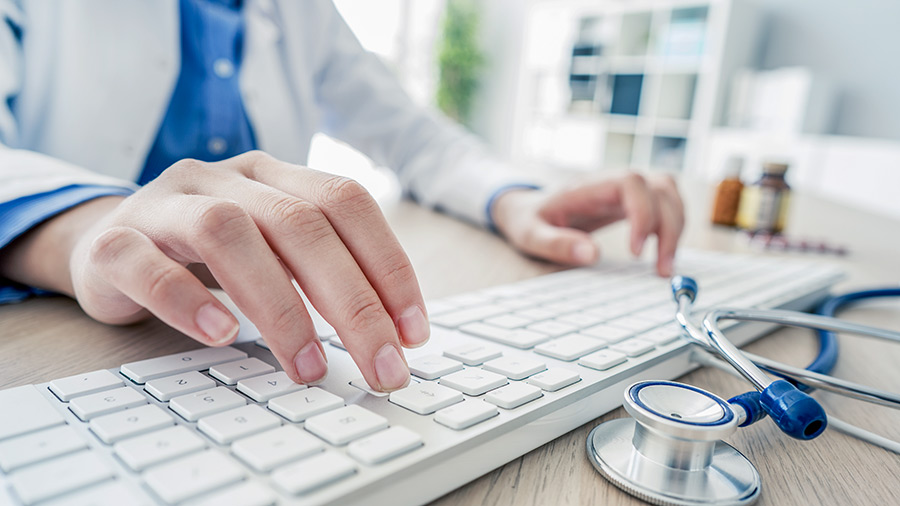 Hands of doctor typing on keyboard